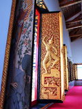 Golden engraved wood door panel in Thailand temple. Royalty Free Stock Photos