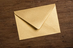 Golden envelope. Golden envelope on wooden table Royalty Free Stock Photography