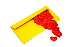 Golden envelope with hearts falling out of it, on an isolated white background stock photo