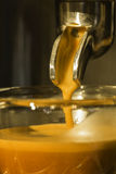 Golden espresso flowing from single portafilter into the cup Stock Photography