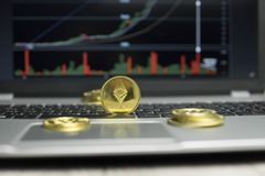 Golden Ethereum coin with gold coins lying around on a black keyboard of silver laptop and diagram chart graph on a stock images
