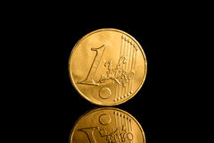 Golden euro coin on a black reflecting background. Golden euro coin on a black reflecting surface. The coin is made of chocolate. frontal view Stock Photo