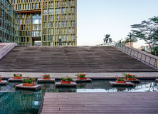 A golden exterior of a modern building with a pond and flowers outdoor. Royalty Free Stock Photography