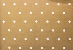 Golden fabric and a white tiny polka dots background stock image