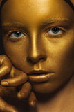 Golden Face. Woman with Luxury Gold Make-up. Fantasy. Face of Styled Enigmatic Woman with Gold Make-up. Luxury Royalty Free Stock Photography