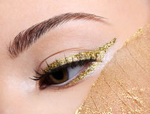 Golden fashion eye  make-up. Fashion make-up in golden eyeliner arrow on the female with a yellow leaf Stock Photo