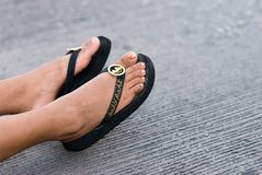 Golden Feet. A woman's feet stratch out on pavement Stock Photography