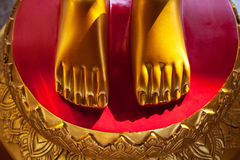Golden feet on a red background vivid close-up. Asian shrine sculpture Royalty Free Stock Image