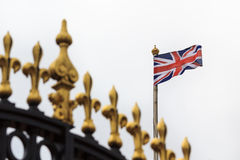 Golden fence of Buckingham Palace with union jack. Top of golden fence of Buckingham Palace with waving union jack Stock Photo