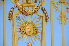 Golden fence with ornament. Sun face near the castle of Versailles palace in France. Ornaments of flowers and needles on the wall against the blue sky stock image