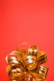 Golden festive bow on red Royalty Free Stock Image