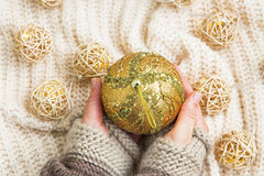 Golden festive Christmas ball decoration in woman hands Stock Image