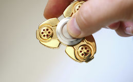 Golden fidget spinner toy on dark aurface Royalty Free Stock Photo