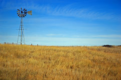 Golden Field Windmill. A windmill sits atop a golden field of grass Royalty Free Stock Image