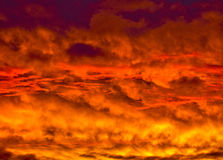 Golden Fiery Sunset with layered Clouds Stock Photo