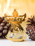 Golden figure of Christmas angel, pine cones, sparkling background, festive, greeting card template Royalty Free Stock Photo