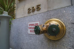 Golden fire hydrant sprinkler connection in a wall in New York City Stock Photography