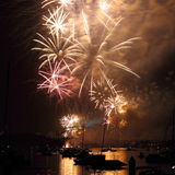 Fireworks golden over harbor. Golden colored fireworks display over harbor with the smoke wandering off (NYE, Sydney, Australia) - view from Parramatta Stock Photo