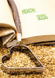Golden flax seeds with cookbook and heart Stock Photography