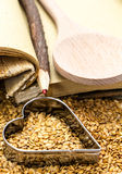 Golden flax seeds with cookbook and heart. Closeup Royalty Free Stock Image