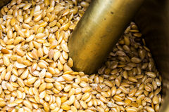 Golden flax seeds inside bronze mortar Stock Photography