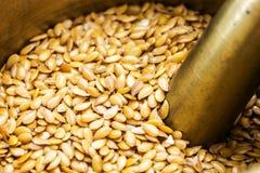 Golden flax seeds inside bronze mortar Stock Photo