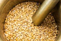 Golden flax seeds inside bronze mortar Stock Photos