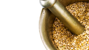 Golden flax seeds inside bronze mortar Royalty Free Stock Image