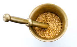 Golden flax seeds inside bronze mortar Stock Image