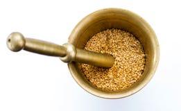 Golden flax seeds inside bronze mortar Stock Image
