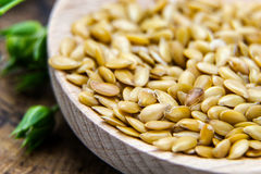 Golden flax seeds wooden surface Royalty Free Stock Photography