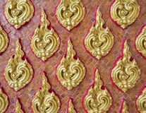 Golden floral pattern in the traditional Thai style. Golden floral pattern in the traditional Thai style on the church wall of Thai temple Stock Photo