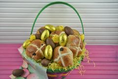Golden foil chocolate eggs with cute Easter chick decorations and hot cross buns Royalty Free Stock Image