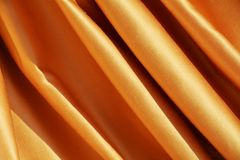 Golden folds. The drop of the golden textile creates large beautiful soft folds, the image having an inner dynamism generated by the oblique lines formed by the Royalty Free Stock Photography