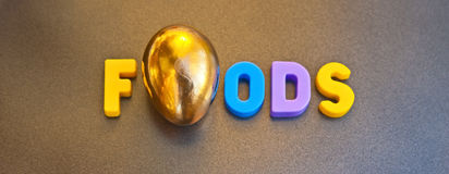 Golden foods. Text ' foods ' in colorful uppercase letters where one letter ' o ' has been replaced by a golden egg, concept image for possible logo Royalty Free Stock Photography