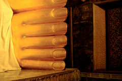Golden foot is part of huge reclining Buddha statue in a famous Stock Photos