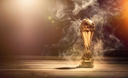 Golden footbal trophy cup with smoke on table and lens flares. Gold football or soccer sports trophy cup on wood desk with dramatic strong contrast light, shadow royalty free stock photos