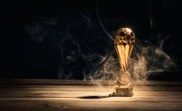 Golden footbal trophy cup with smoke on table. Sports trophy cup on wood desk with dramatic strong contrast light and shadow royalty free stock image