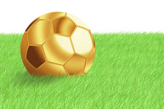 Golden football ball on green grass Stock Photos