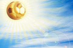 Golden football ball shining over sky. Royalty Free Stock Image
