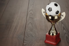 Golden football trophy cup. Golden football soccer trophy cup on the wooden table royalty free stock photo