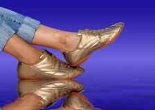Golden footwear. On the water royalty free stock images