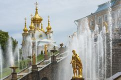 Golden fountains in Peterhof near Saint Petersburg. Famous golden fountains in Peterhof near Saint Petersburg with baroque ornate church on background royalty free stock images