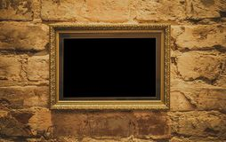 A golden frame with a beautiful decorative baguette hangs on a golden antique wall stock photography