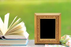 Golden frame with books on wooden table stock images