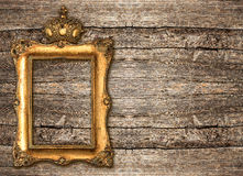 Golden frame with crown over wooden background Royalty Free Stock Photo