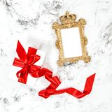 Golden frame gift box red ribbon bow Flat lay. Golden frame, gift box red ribbon bow. Flat lay marble background Royalty Free Stock Images
