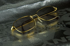 Golden frame glasses. A golden frame glasses silver packaging bag Royalty Free Stock Images