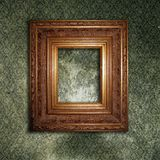 Golden frame on a green wallpaper Royalty Free Stock Photos