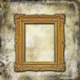 Golden frame on grunge texture. An empty glden decorated frame on a grunge victorian wallpaper stock images
